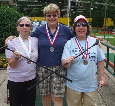 Helena Cribb, Linda Zappacosta, and Linda Desiderio proudly wear their medals.