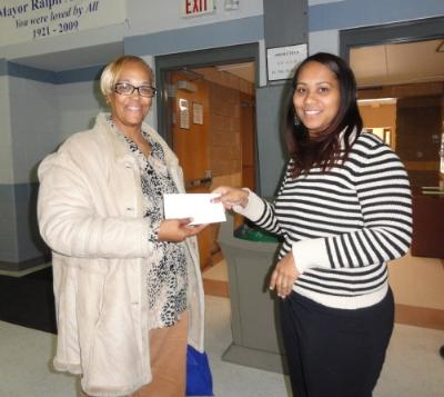 Christy Bobo (right), Housing Director at COSA, presents raffle winner Yvette Cauthorn (left), of Chester a voucher to be used for home heating oil this winter.