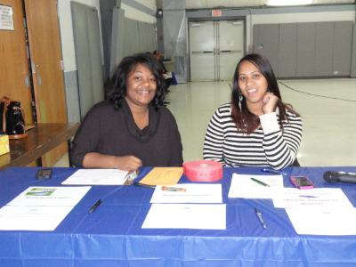 Katrina Lewis (left), of COSA, and Christy Bobo (right), COSA Housing Director, register Energy Fair guests.