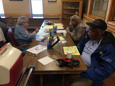 Care receivers Penny Marinakis, Gloria Thompson, and Herbert Pembleton participate in a Creative Arts activity.