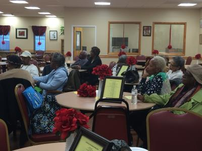 "Caregivers listen to the presentation on ""Understanding Fraud and other Common Preventable Concerns and Misconceptions."""